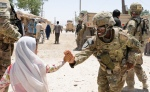 Staff Sgt. Samira Abdullahmuhammad with a female engagement team, 40th Engineer Battalion, 170th Infantry Brigade Combat Team, gives a high-five to a child during a mission to deliver medical supplies to a clinic in Deh Dadi, Afghanistan, June 1.